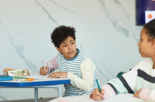 Portret van een jonge jongen die met een vriend praat terwijl hij aan het bureau zit in de klas van de school, kopieer ruimte