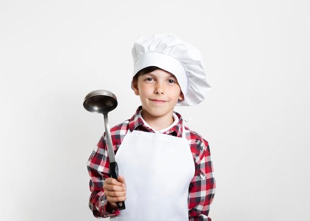 Portret van een jonge jongen die zich voordeed als chef-kok