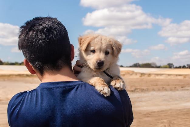 Portret van een jonge jongen die zijn hondje draagt.