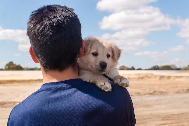 Portret van een jonge jongen die zijn kleine puppy op het strand draagt.