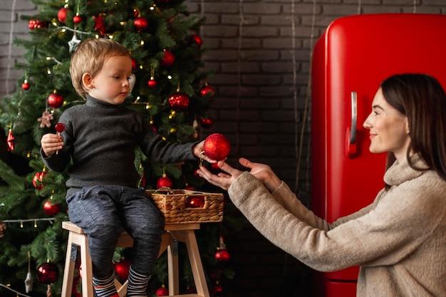Portret van een jonge jongen naast de kerstboom
