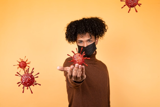 Portret van een jonge jongen van het afrohaar met medisch masker op een gele achtergrond die een bacteriële molecule houdt. epidemie, virus, gezondheid. kopieer ruimte