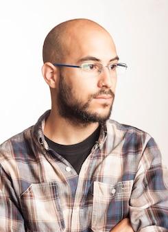 Portret van een jonge kale man met een baard en een bril