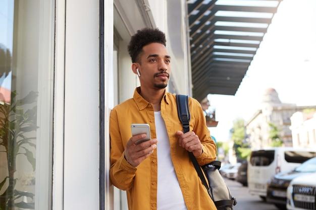 Portret van een jonge kalme donkere man in een geel overhemd op straat loopt, telefoon houdt, chatten met vriendin, kijkt bedachtzaam.
