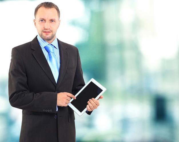 Portret van een jonge kantoormedewerker die een tabletcomputer gebruikt in zijn kantoor
