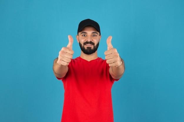 Portret van een jonge kerel die een duim omhoog tekent tegen blauwe muur.