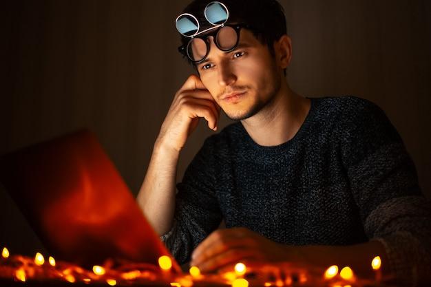 Portret van een jonge kerel die schaduwen draagt, die bij laptop in huis van de donkere kamer werkt