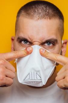 Portret van een jonge kerel in een close-up van het gasmasker op een gele ademhalingsbescherming tegen het virus. het concept van coronavirus.
