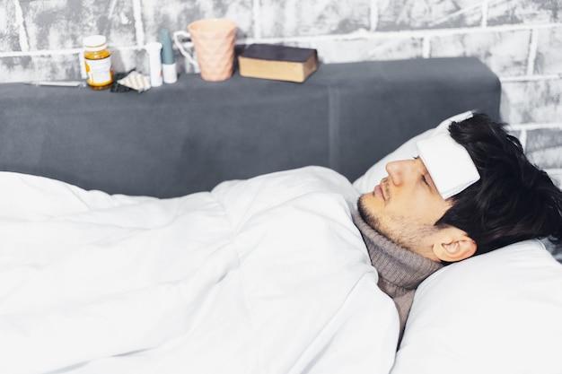Portret van een jonge kerel liggend op bed met temperatuur, kompres op voorhoofd naast medicijnen en kopje thee.
