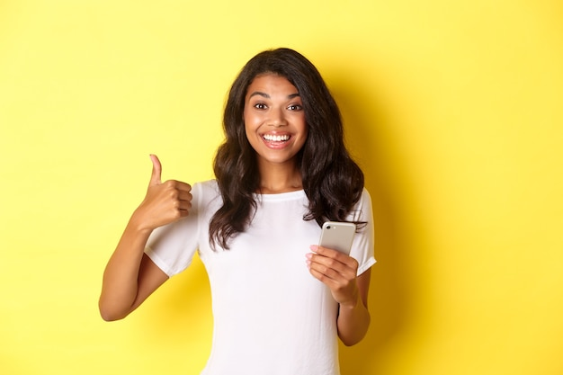 Portret van een jonge knappe afro-amerikaanse vrouw die thumbsup laat zien tijdens het gebruik van app-apps voor mobiele...
