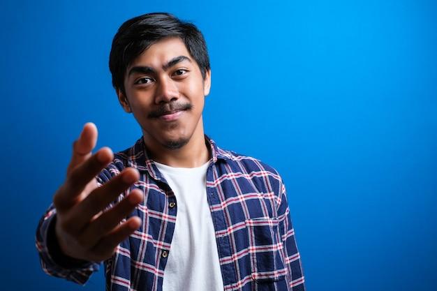 Portret van een jonge knappe aziatische student die een flanellen overhemd draagt dat handdruk aanbiedt tegen een blauwe geïsoleerde achtergrond. overeenkomst concept:
