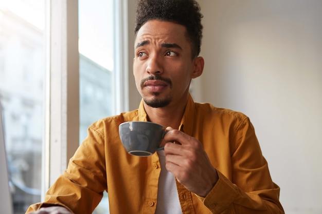 Portret van een jonge knappe donkere denkende man, drinkt aromatische koffie uit een grijze camera en kijkt bedachtzaam weg. zou hij gewoon barista willen zijn?
