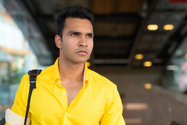 Portret van een jonge knappe indiase man buiten het metrostation