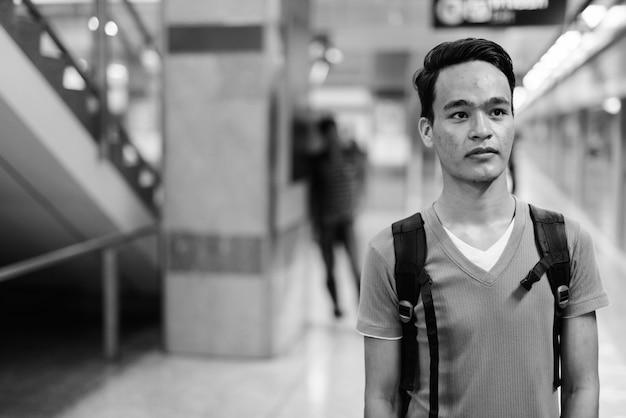 Portret van een jonge knappe indiase man op het metrostation van bangkok in zwart-wit