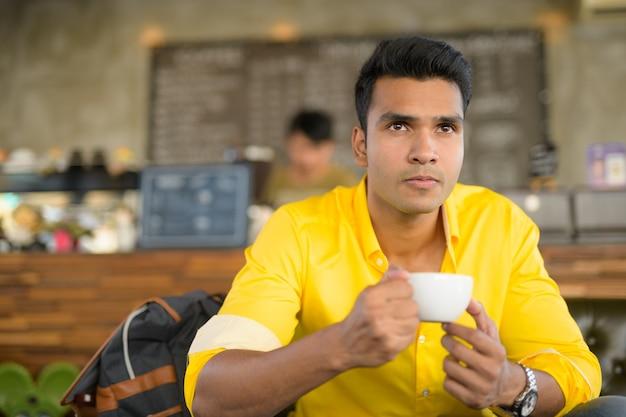 Portret van een jonge knappe indiase man zit in de coffeeshop