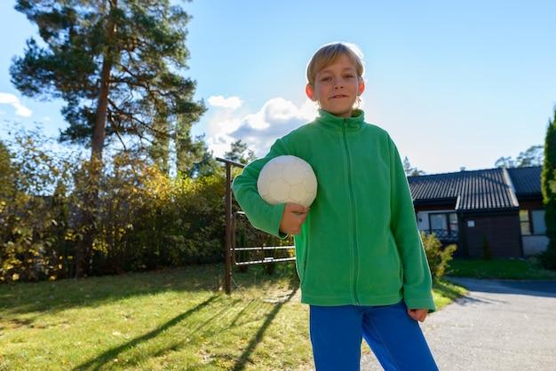 Portret van een jonge knappe jongen met blond haar in de voortuin thuis