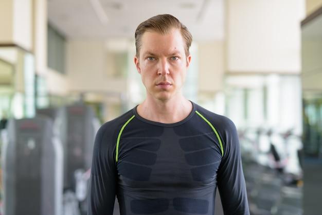 Portret van een jonge knappe man in de sportschool tijdens covid-19