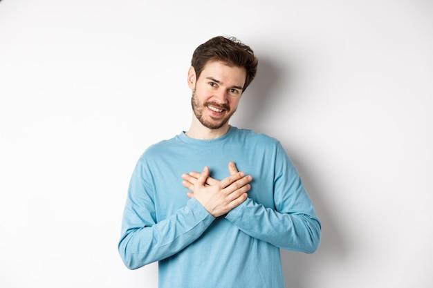 Portret van een jonge knappe man met baard, hand in hand op hart en bedankje zeggen, na te denken over aangenaam moment, staande op een witte achtergrond.