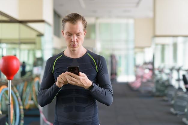 Portret van een jonge knappe man met behulp van telefoon in de sportschool tijdens covid-19