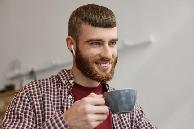 Portret van een jonge knappe man met een rode baard die breed lacht en geniet van heerlijke gebrouwen koffie, gekleed in basiskleding.