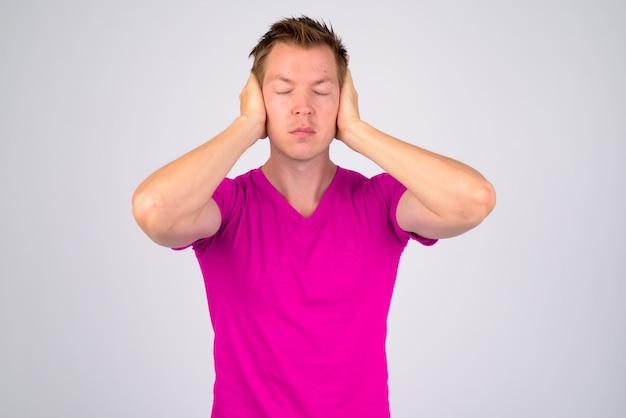 Portret van een jonge knappe man met paars shirt tegen een witte muur