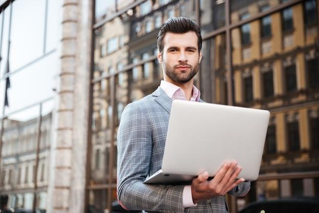 Portret van een jonge knappe mens in laptop van de jasjeholding