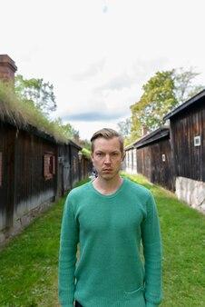 Portret van een jonge knappe scandinavische man in het midden van uitgelijnde oude houten huisjes