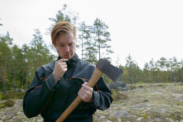 Portret van een jonge knappe scandinavische man klaar om te oogsten in het bos buiten