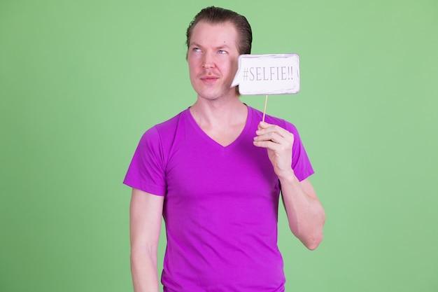 Portret van een jonge knappe scandinavische man met paars shirt tegen chromakey