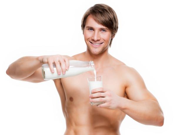 Portret van een jonge knappe spiermens die melk in een glas giet - dat op witte muur wordt geïsoleerd.