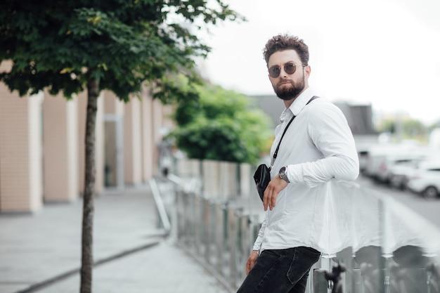 Portret van een jonge knappe stijlvolle man in een wit overhemd in de straten van de stad in zonnebril