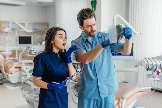 Portret van een jonge knappe tandarts die bij haar collega staat en röntgenfoto's vasthoudt.