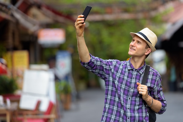 Portret van een jonge knappe toeristenmens die met telefoon in de straten vlogt