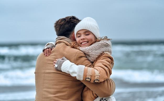 Portret van een jonge knappe vader met zijn geliefde mooie dochter op het strand in de winter.