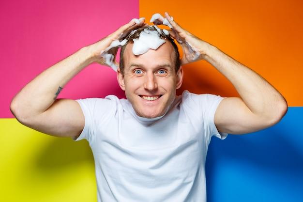 Portret van een jonge, knappe, vrolijke man op een veelkleurige achtergrond, gekleed in een wit t-shirt, creëert een modieus kapsel, domme en positieve emoties
