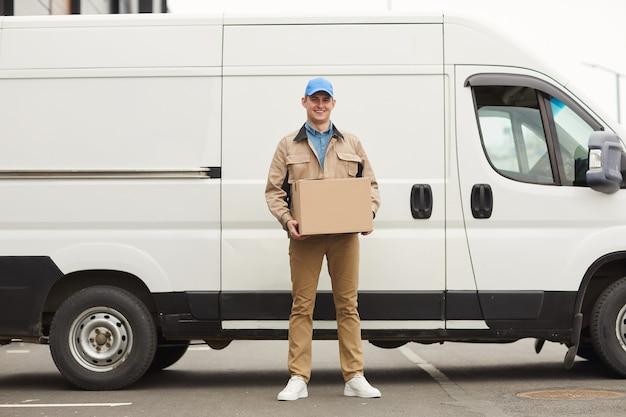 Portret van een jonge koerier die kartonnen doos in zijn handen houdt en camera bekijkt terwijl hij buitenshuis tegen het busje staat