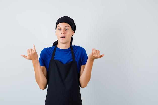 Portret van een jonge kok die een telefoongebaar in t-shirt, schort toont en aarzelend vooraanzicht kijkt