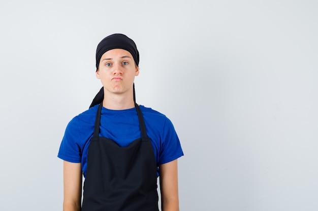 Portret van een jonge kok die zich voordeed terwijl hij in een t-shirt, schort en aarzelend vooraanzicht staat