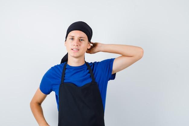 Portret van een jonge kok die zijn hoofd krabt terwijl hij zijn hand op de heup houdt in een t-shirt, een schort en een peinzend vooraanzicht