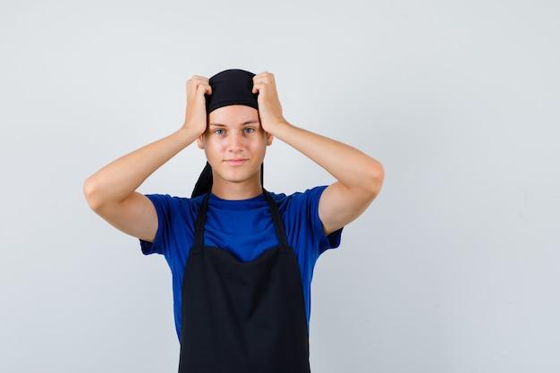 Portret van een jonge kok met handen op het hoofd in t-shirt, schort en vergeetachtig vooraanzicht