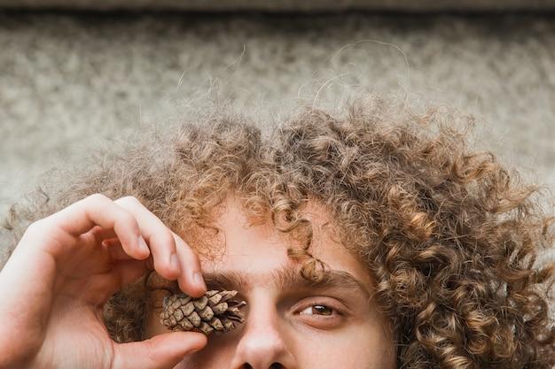 Portret van een jonge krullende haired kerel in een de zomerpark