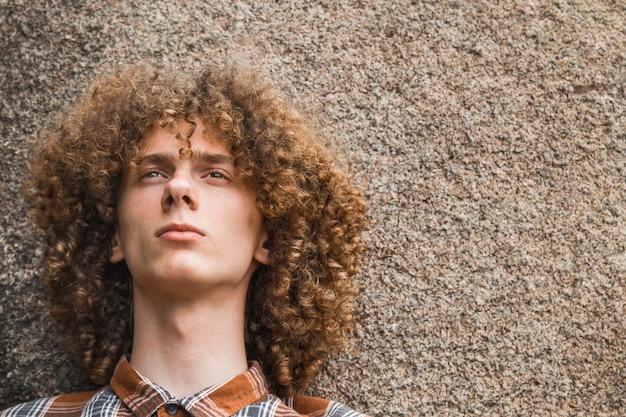 Portret van een jonge krullende haired kerel onder de stenen