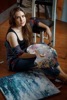 Portret van een jonge kunstenaar omringd door schilderijen