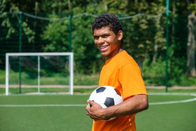 Portret van een jonge lachende spaanse man die een voetbal vasthoudt terwijl hij buiten op het sportveld staat tegen een voetbaldoel