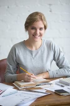 Portret van een jonge lachende student aan de tafel