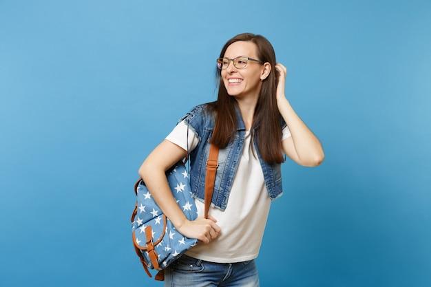 Portret van een jonge lachende studente met een rugzak die een bril draagt en opzij kijkt terwijl ze haar kapsel corrigeert dat op een blauwe achtergrond wordt geïsoleerd. onderwijs in het concept van de middelbare schooluniversiteit.