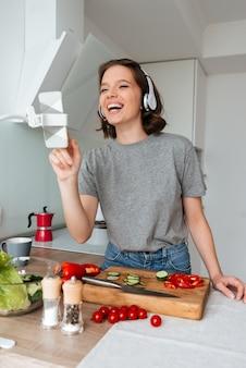 Portret van een jonge lachende vrouw met een koptelefoon