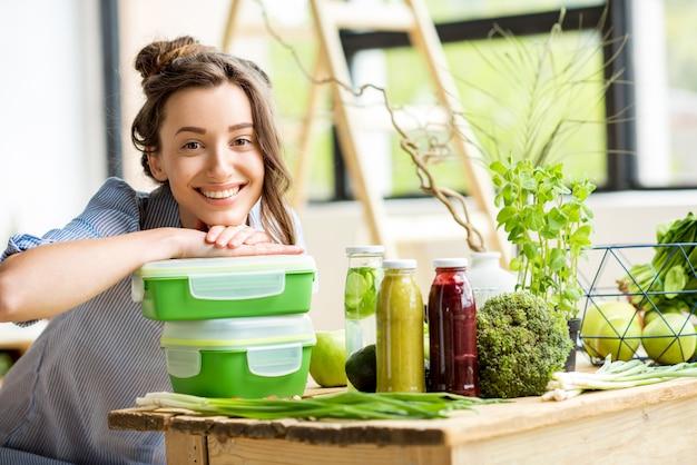 Portret van een jonge lachende vrouw met groene lunchboxen binnenshuis