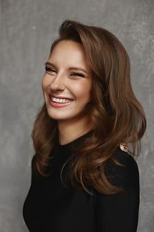 Portret van een jonge lachende vrouw met lichte make-up en perfecte huid in een zwarte jurk