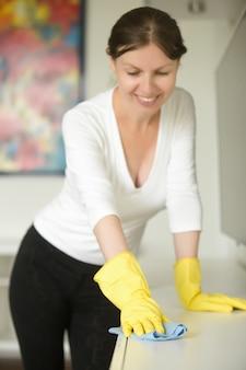 Portret van een jonge lachende vrouw met rubberen handschoenen schoonmaken